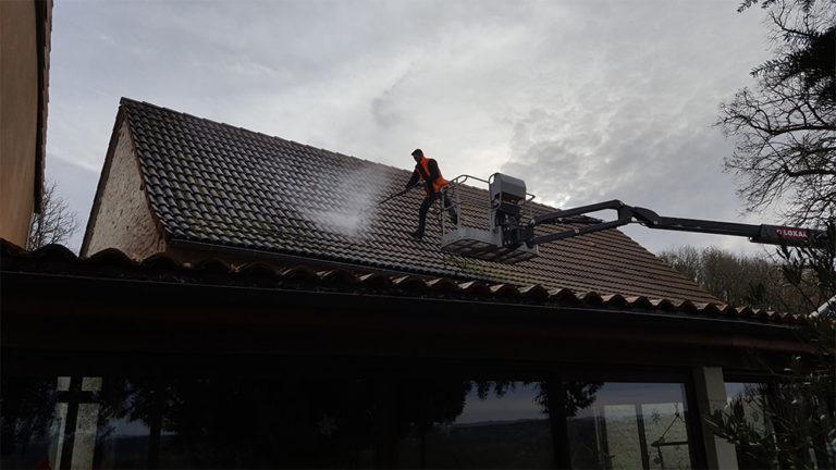 Homme en train de faire du nettoyage haute pression sur le toit d'une maison